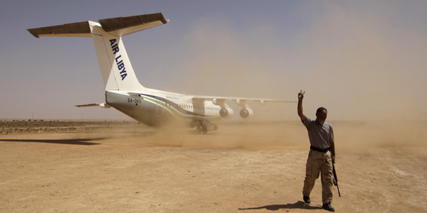 A rebel flashes a victory sign as he walks near an Air Libya aircraft at Rhebat air strip